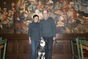Christiane Borgeat et Jean Barré avec leur chienne devant une fresque d'une salle du pub Saint-Patrick