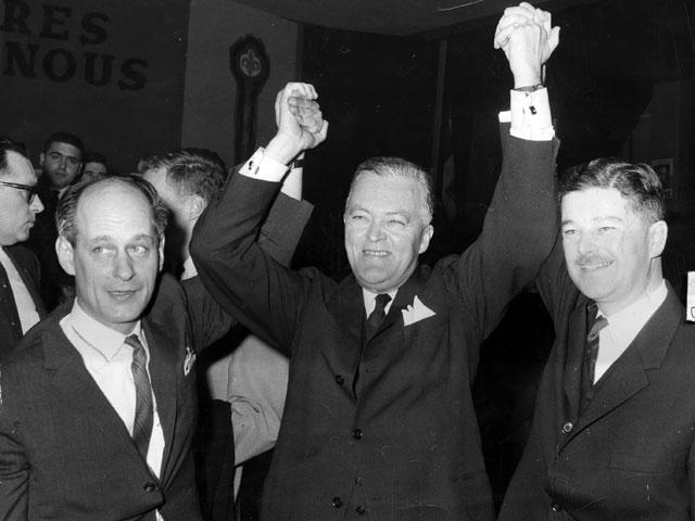 Jean Lesage, célèbrant la victoire des siens en compagnie de ses deux candidats vedettes, René Lévesque et Paul Gérin-Lajoie